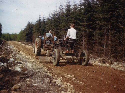 Farm machinery grading a forest track