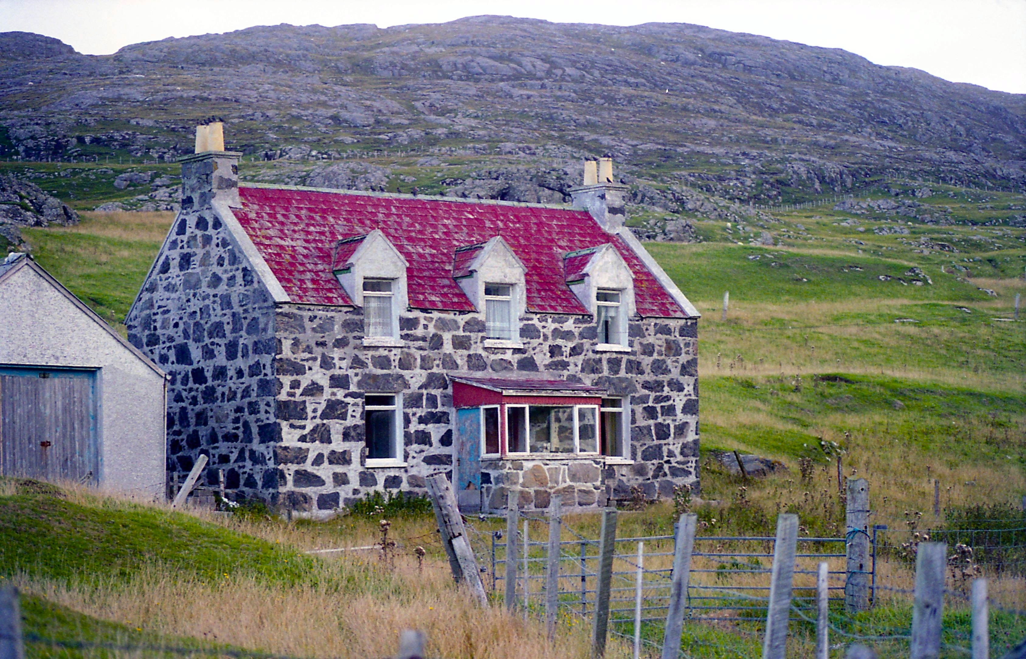 Image of a croft house in front of a hill in rural Scotland.